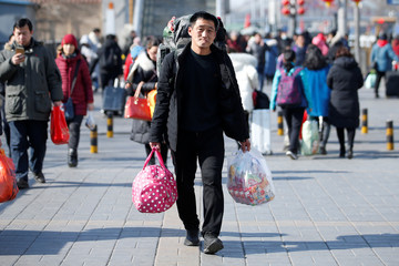A passenger leaves Beijing Railway Station  as the annual Spring Festival holidays end in Beijing