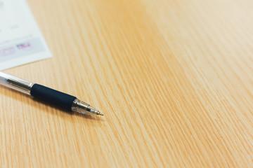 pen on wooden desk of office