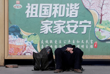 A passenger takes a nap against a poster promoting the Chinese Core Socialist Values at Beijing Railway Station as the annual Spring Festival holidays end in Beijing