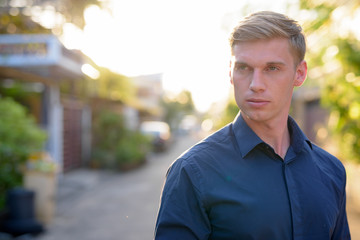 Face of young handsome businessman with blond hair thinking outdoors
