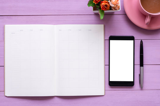 Mobile smart phone with blank white screen,weekly planner notebook,pen and cup of coffee  isolated on pink wooden table background.