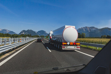 fuel truck driving on the highway, white empty oil tank, cargo transportation, rear perspective view