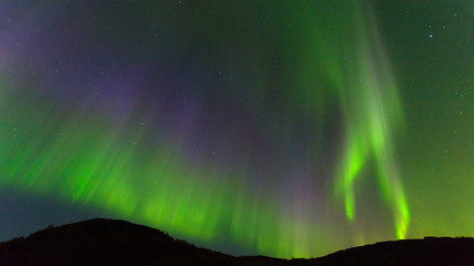 Northern, aurora borealis in the sky above the hills. Violet and green. Color.