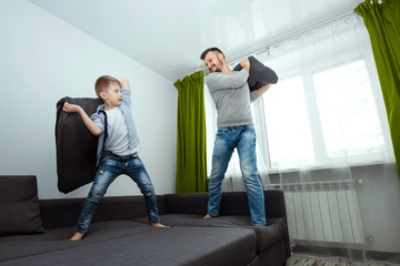 Happy family, Dad and son spend time together, fooling around on the bed, beating with pillows. Concept of happy father's day, family enthusiasm, spend time together, copy space.