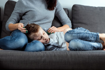 The boy is lying on the couch with an abdominal pain near his mother. The concept of custody, parental care, stomach problems, food poisoning, problems in children.
