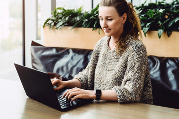 Happy woman millennial using laptop while sitting at cafe.Young businesswoman sitting in coffee shop,working on computer