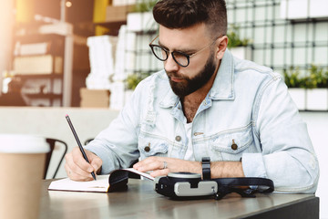 Young bearded hipster man sits in cafe at table, writes in notebook. Journalist writes information in notepad.