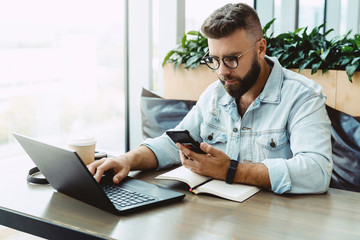 Hipster man sits in cafe, uses smartphone, works on laptop. Businessman reads an information message in phone. Freelancer works outside office. Teleworking. Online marketing, education for adult.