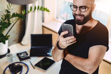 Portrait smiling handsome man reading text message, standing indoors.Businessman sends messages.Stylish brunette hipster uses mobile phone at home. Guy is chatting online. Man browsing social network.