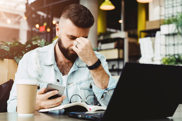 Young bearded sad businessman is sitting at table, covering his face with his hand and holding smartphone in his hand. Man got bad news, problems. Stressed.On desk is laptop, notepad, cup of coffee.