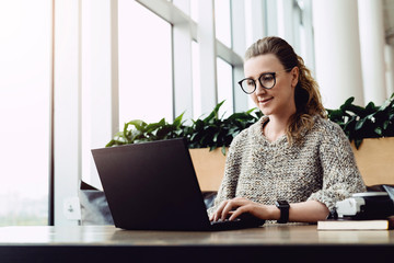 Happy caucasian woman millennial using laptop while sitting at cafe. Young businesswoman sitting in coffee shop, working on computer. Online marketing, business education for adult, teleworking.