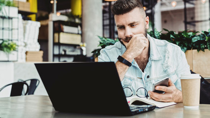 Millennial businessman sitting in cafe with open laptop, looking thoughtfully at computer screen. Male entrepreneur working on computer in modern office, looking anxiously and excitedly at monitor.