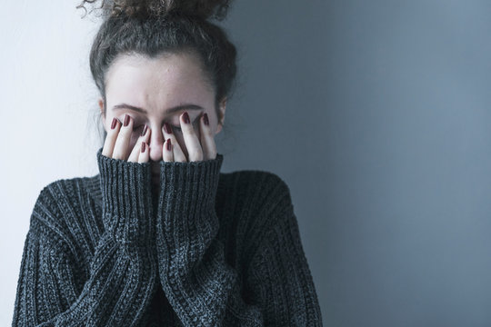 Close up of teenager with depression and bulimia sitting alone in dark room. She covers her face with hands. Mental problems with depression and bulimia.