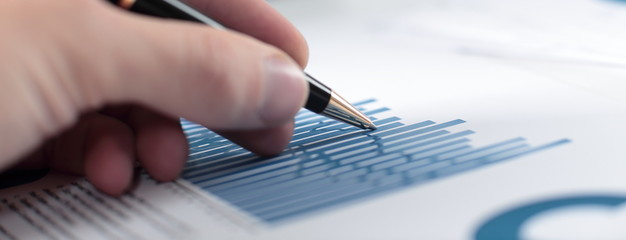 close up.the businessman checks the financial report