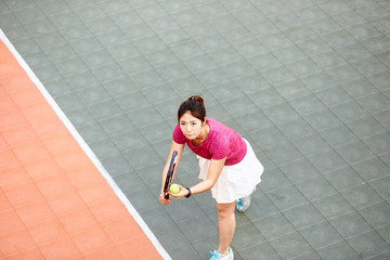 young asian girl playing tennis