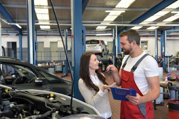 Kundendienst in der Autowerkstatt - Monteur übergibt Autoschlüssel nach Reparatur an Kundin // Customer service in the car repair shop - mechanic hands over car key to customer after repair