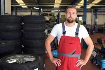 Portrait freundlicher Automechaniker in der Werkstatt für Reifenwechsel // Portrait of a friendly car mechanic in the workshop for tyre changes