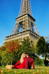 Romantic couple having picnic on the grass near the Eiffel tower