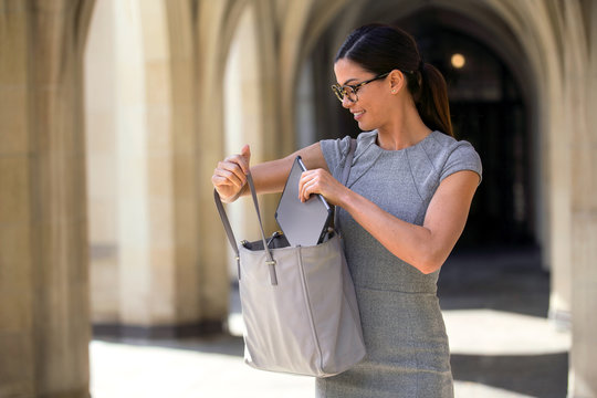 Lifestyle traveling business person putting smart tablet in her bag, convenience