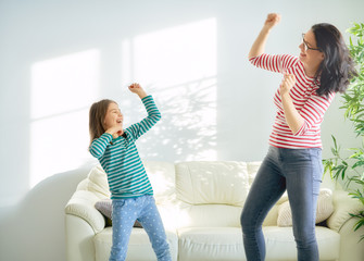 Mother and daughter dancing together