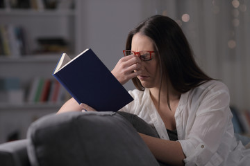 Lady with eyeglasses suffering eyestrain reading book in the night
