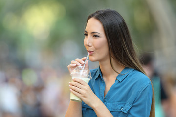 Happy woman sipping milk shake in the street