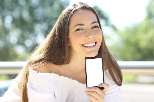Happy woman showing blank phone screen outside