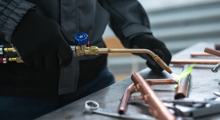 Worker is soldering a pipe by a blow lamp on a factory workbench background. Pipework.