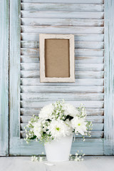 White flowers bouquet against wooden shutters