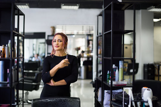 Beautiful young hairdresser in beauty salon