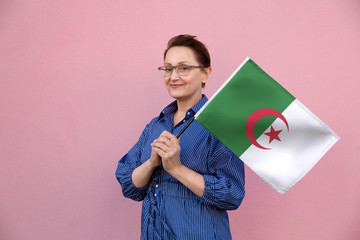 Algeria flag. Woman holding Algerian flag. Nice portrait of middle aged lady 40 50 years old holding a large flag over pink wall background on the street outdoor.
