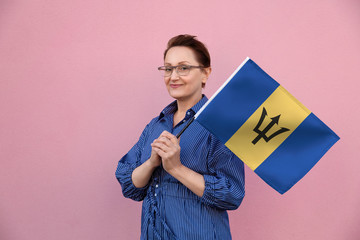 Barbados flag. Woman holding Barbados flag. Nice portrait of middle aged lady 40 50 years old holding a large flag over pink wall background on the street outdoor.