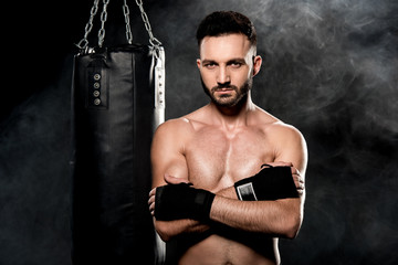 athletic man standing with crossed arms near punching bag on black with smoke