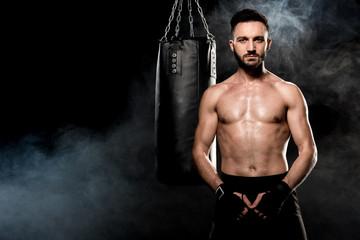 athletic shortless man standing near punching bag on black with smoke