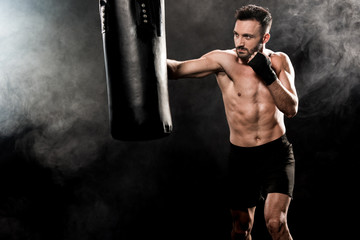 handsome athletic boxer exercising with punching bag on black with smoke