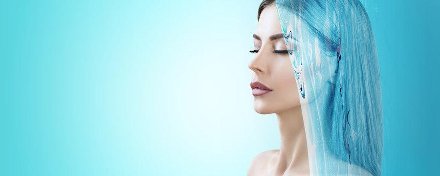 Sensual woman under water splash over blue background.