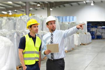 Chef und Arbeiter im Warenlager beim Gesüräch // Workers in logistics - manager and worker in business meeting