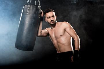 thoghtful athletic boxer holding punching bag on black with smoke