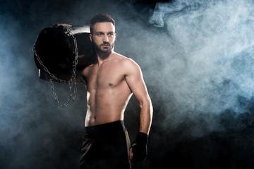 9b4403873b8c shortless boxer holding punching bag on shoulder on black with smoke