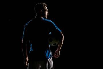 silhouette of muscular sportsman holding ball isolated on black