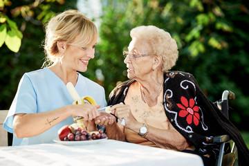 Pflegerin hilft Seniorin beim Obst schälen