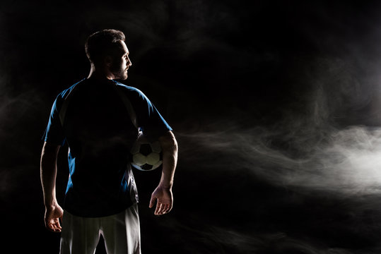 silhouette of football player holding ball on black with smoke