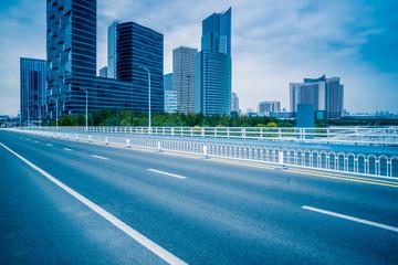 road through the bridge with city skyline backgroun