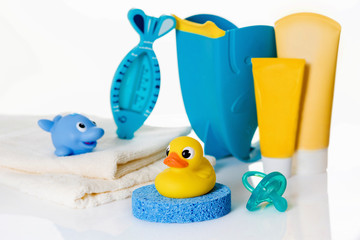 Still life with baby hygiene and bath items,    towel, pacifier, rubber toy, thermometer