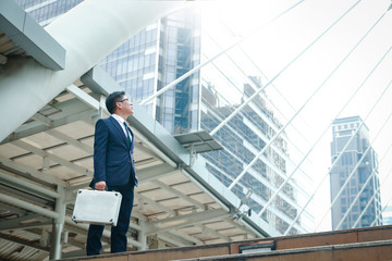 An Asian businessman holding a bag looking up at a tall building. Have space to write text