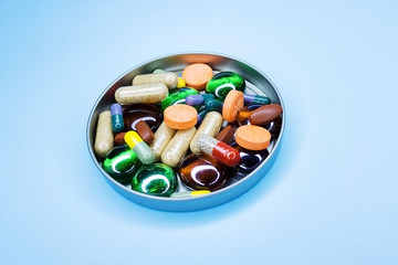Different pills in a jar. Different pills flying away from open plastic bottle isolated on white