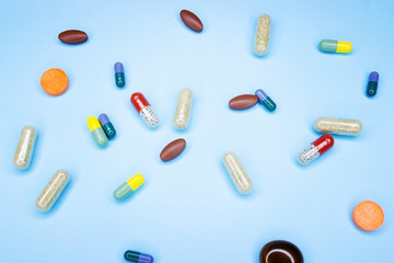 Different pills on a blue background. A photo of different medical drugs, tablets and pills on blue background Pretty pills.