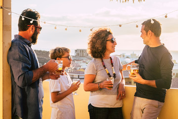 Group of middle age people caucasian men and woman drink together on the terrace with city view having fun and friendship - blonde kid with them - outdoor home leisure activity for friends