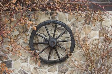 Old wooden wheel on the wall ,autumn