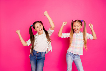 Close up photo two little age girls holiday dancing glad hands up children festive mood win boys video game wearing casual jeans denim checkered plaid shirts isolated rose vivid vibrant background